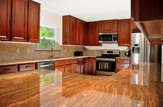 high gloss faux wood block counters; dark cherry cabinets; stainless steel appliances; full kitchen remodel renovation... by the BEST custom construction company in central Florida | www.allinconstruction.com