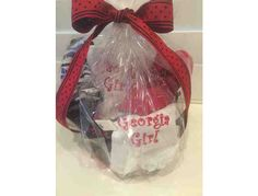 This auction item is for a UGA baby girl basket filled with a silver pacifier clip, two bibs, a burp cloth, a hat and fancy pants. The bibs, burp cloth, hat, and fancy pants are embroidered with a UGA theme. For your little Georgia Girl, or a gre...