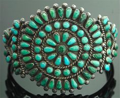 Vintage Zuni petitpoint cluster. With wear and body oils, many of the stones have darkened or turned green. This is typical of natural blue Sleeping Beauty turquoise, long a favorite of Zuni artists.