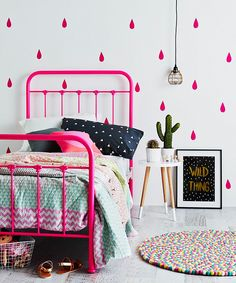 Chambre d'enfant avec un lit en fer forgé rose fluo flashy, linge de lit fluo, suspension baladeuse fil noir, stickers gouttes de pluie rose fluo, table de chevet scandinave bois clair et blanc, cactus vert, affiche graphique