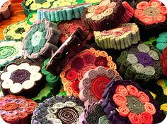 Re-purposed wool, cut into strips and then rolled and sewn into circles to make a larger circle.  Could then be made into pins, ornaments, pincushions, or all sewn together to make a rug or table runner.