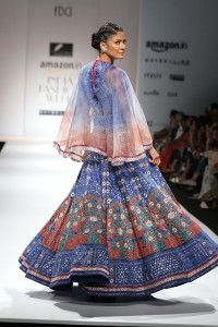 AIFW SS16: Poonam Dubey chose cornflower blue & red for her lehnga collection.  Coupled with her unique treatment of the dupatta (or illusion of one), the entire line was fresh and breezy.  Read more: 13 Faves: Amazon Indian Fashion Week 2016 http://desi-stylebook.com/2015/10/13-faves-amazon-indian-fashion-week/
