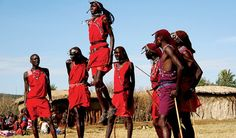 Group of Masai villagers chanting and jumping in a Kenyan ceremony
