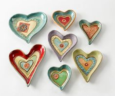 Heart Dishes by Laurie Pollpeter Eskenazi. Vibrant colors bring out the whimsical patterns and textures of these hand-built stoneware clay dishes. Perfect as gifts, they add artistry to your decor while holding anything from candy to jewelry. Each is glazed by hand with small brushes to bring out the detail in pattern and texture. All glazes are food safe. Hand washing is recommended to avoid breakage.Shown in primary image, clockwise from top left: Tranquility Heart, Sunshine Heart, Lacy…