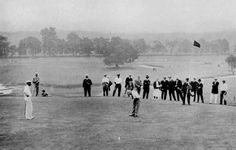 1915 US Open Golf Championship Photo Gallery, French Professional Louis Tellier holing a putt on the 11th green. His dapper partner, 1914 US Open Champion, The Great Walter Hagen looking on.