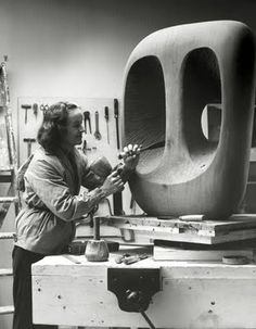 English sculptor Barbara Hepworth in the Palais studio (1963) with unfinished wood carving 'Hollow Form with White Interior,' photographed by Val Wilmer. via the artist's site