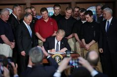 """U.S. President Donald Trump signs an executive order on """"energy independence,"""" eliminating Obama-era climate change regulations, during an event at the Environmental Protection Agency (EPA) headquarters in Washington, U.S., March 28, 2017. Photo by Carlos Barria/REUTERS"""