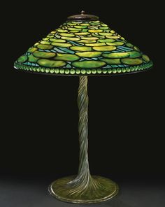 "Tiffany Studios ""LILY PADS"" TABLE LAMP with a rare ""Water Lily Twisted Stem"" base shade with small early tag impressed TIFFANY STUDIOS/NEW YORK base impressed TIFFANY STUDIOS/NEW YORK/443 leaded glass and patinated bronze, circa 1905."