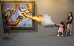 Members of a family pose for a photograph in front of a 3D painting at the 2012 Magic Art Special Exhibition in Hangzhou, Zhejiang province July 7, 2012. The exhibition will be open till August 6