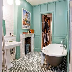 Gorgeous mint green bathroom with mosaic patterned floors, grey claw foot tub and a retro poster.