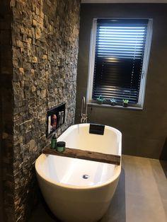 Een mooie badkamer in spa sfeer. Met een vrijstaand bad en een vrijstaande badkraan in geborsteld nikkel. Een betonlook tegel met als accent een natuursteen wand.