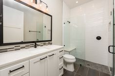 Custom tile work, a standing shower and large vanity with tons of storage adorn a third bathroom! Custom Home Designs, Custom Home Builders, Custom Homes, Standing Shower, Japanese Minimalism, Design Firms, House Plans, Vanity, House Design