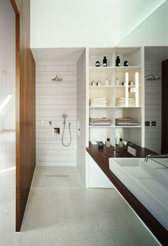 ABSOLUTELY LOVING IT! white terrazzo floors, white tile walls and wood. Trough sink, walk in shower.