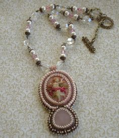 February Challenge .. B'sue Cameo was used in this necklace .. Cameo is hand painted using alcohol inks and a Rose quart fits in perfect beneath the cameo .. I used pearls and size 8 .. 11 and 15 seed beads around the entire focal piece .. chain has pearls .. pink crystals and clear glass beads .. brass caps  clasp .. Designed by Jann Tague .. Clever Designs .. https://www.facebook.com/#!/JewelsByJann