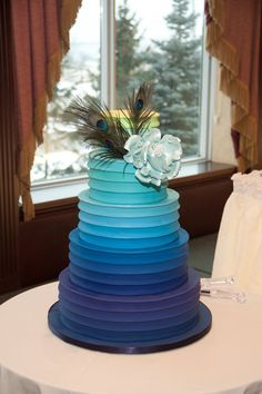 Five tier blue ombre cake with ribbed icing detail and peacock feather cake topper