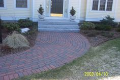 A brick walk-way with split-top thermal granite steps into the home.