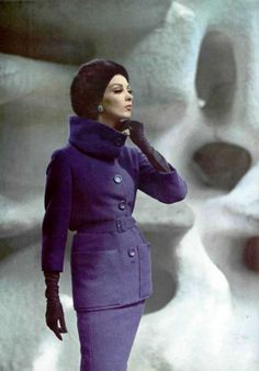 Wilhelmina in purple wool suit with longer jacket, belted and high stand-up collar worn with mink hat by Jacques Heim, photo by Pottier, 1962