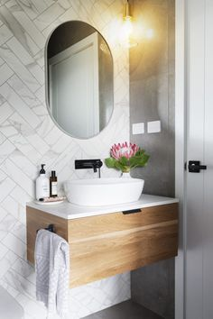 Denman Prospect Residence - Studio Black Interiors. Guest ensuite and powder room. Double herringbone marble look tiles, wall hung timber vanity with stone top and oval mirror. Built by Homes by Howe. Photography by HCreations.