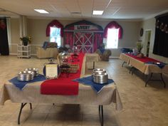 Serving line with a Barn as a focal point.    They have great displays at Shindigz.com.   We draped the windows with red jute.   Notice the cute tin pie plates we used for their food.   Ordered in bulk from KaTom.com.   We printed out the menu and put one of our jean chargers behind it.