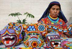 Una indígena huichole, proveniente del estado de Jalisco y ataviada con su ropa típica, ofrece máscaras elaboradas con chaquiras de colores en el centro histórico de la capital mexicana.