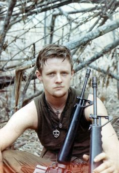 American soldier with a piece symbol and cross hanging from his neck and two M16's - Vietnam War
