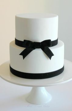"""'Coco' This two-tier white cake with black velvet ribbon is inspired by a beautiful quote I came across recently: """"Simplicity is the keynote of all true elegance"""" Coco Chanel White Birthday Cakes, Blue Birthday, Chanel Cake, Chanel Party, Coco Chanel, White And Gold Wedding Cake, White Cakes, Engagement Cakes, Gold Cake"""