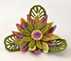 "This is a handmade fine thread crochet flower daisy brooch. The flower itself measures 3"" (7.5 cm) wide and is done in a variegated thread that includes shades yellow, purple and rose. There are 15 petals on the daisy, and each petal has been accented with chartreuse green stitching. There is also a mini daisy which has an additional 8 petals in matching green with a button center. There are 3 medium olive green leaves in the background....simply put...WOW"