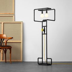 Fun design floor lamp with creative and playful knob dimmer. Here in black patina metal finish with yellow braided cord and yellow knob. Shown in urban loft apartment.