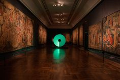 A spinning disk installation covered in changing glowing patterns illuminates the dimly lit Tapestry Gallery in London's V&A museum.
