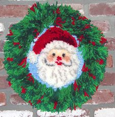 """There's Santa peering in through the wreath to see if you've been good or bad! This perfect wall or door hanging measures 16"""" across and has added interest with 5"""" yarn being used for the wreath. Kit comes complete with easy to follow full color graph, blue-lined 3.75-count canvas for easy counting and 100% acrylic rug yarn. Latch hook tool sold separately."""