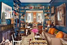 In the library, picture lights from Circa Lighting top the bookcases; the sofa is by Dune   archdigest.com