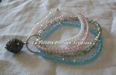 Bracciale con quattro fili di cristallo celeste, grigio, rosa e bianco montati con elastico uniti da un anello in alluminio argentato con ciondolo in metallo perla tipo filigrana antica
