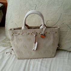 Dooney and Burke Ivory color. A few scuff marks on handles. 3 small stains on bottom. Bags Satchels