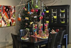 Vibrant colors shine against the dark wood & clean lines of this dining room. Vintage candy & candy buckets add whimsy–sure to thrill children–& jeweled lanterns, tall vases filled with colorful ornaments & votive holders take Christmas decorations in a playful direction.Table runner is a bath rug & tree branch from yard used to hang ornaments. The lime green dishes add to the saturated color scheme.