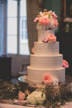 Simple wedding cake adorned with flowers.