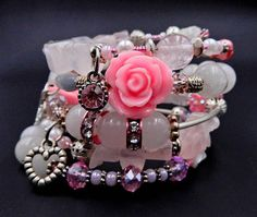 This feminine pink and white beaded coil bracelet is made with an assortment of glass & acrylic beads, Rose Quartz nuggets, Grey Quartz chips, natural White Howlite beads, large pink rose beads, Swarovski crystals, white cats eye chips, silver spacers & tube beads, freshwater pearls, pink gem charm, and 2 silver heart charms for a gorgeous piece of arm candy.   ★ Return to my main shop page here for more inventory ★ www.etsy.com/shop/bridgetollbeading  ★ Read my FAQs below a...