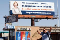 A man who identified himself as a medical marijuana patient poses with a new billboard erected on top of a liquor store in Denver April 6, 2012. Colorado voters will decide in November whether to legalize marijuana for recreational use, regulating it like alcohol products.