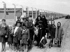 Jewish mothers and children forced walk to the gas chambers, past the barrcks and the electrified barbed wire
