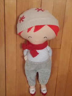 """Leo Soft & Cute is approximately 19"""" tall. His red hair is soft & furry and his body is soft and lovable. He is wearing a tan ski hat with red snowflakes, a red scarf, gray sweat pants and red & white sneakers. His face has been embroidered. He will delight any age."""