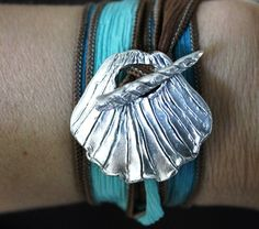 Silk Wrap Bracelet ~ This hand carved scallop shell features an intricately carved corkscrew shell  toggle.  Both pieces are hand carved and cut, and are not made using a commercial mold.  This scallop pod toggle is hand crafted from reclaimed silver. This shimmering toggle is interlaced with a hand dyed silk ribbon with cool hues of blue and brown that wraps end over end around your wrist.