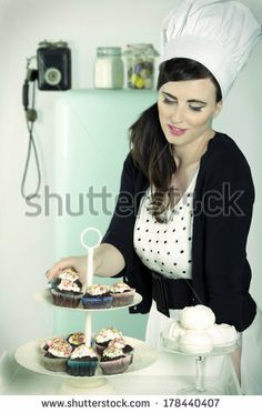 A beautiful girl with a chef hat, puts some cupcakes on a cake stand close to some meringues, in a vintage-like kitchen. by Annalisa Bombard...