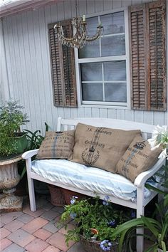 The addition of old shutters by an exterior window..a chandelier and love seat with burlap pillows makes an inviting setting...