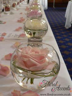 cute floating roses in mini fish bowls or candle cups