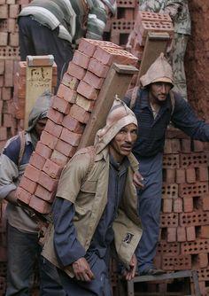 An Egyptian man worker stacks bricks at a brickyard kiln factory near the town of Mansoura city