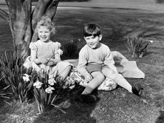 Princess Anne (later The Princess Royal) pictured with Prince Charles (later The Prince of Wales) in the garden of Royal Lodge, Windsor Great Park, in 1954. © Press Association