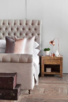 Bed with upholstered headboard, pink scatter cushions, old suitcases and wooden bedside table