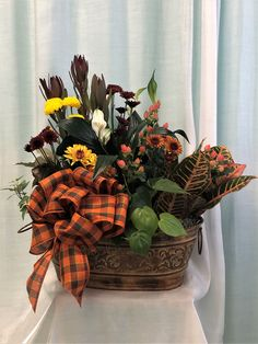 Beautiful autumn dish garden with mums, leucadendron, colorful mums, hypericum berries, lilies, and assorted lush green plants. Presented in a lovely, oval metallic planter with embossed detailing and handles.