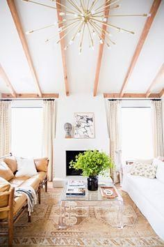 Love this bright, modern tan and white living room with a comfy leather sofa, exposed beams and a stunning brass sputnik chandelier.