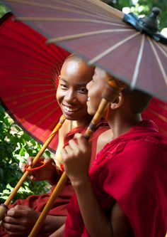 http://www.greeneratravel.com/ Young Monks under umbrella for hide the very hot sunshine