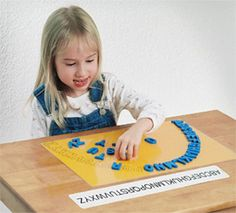 Cute.  I would probably have the kids use tongs of some sort to place the letters and have them placed off to the side opposite of their dominant hand.